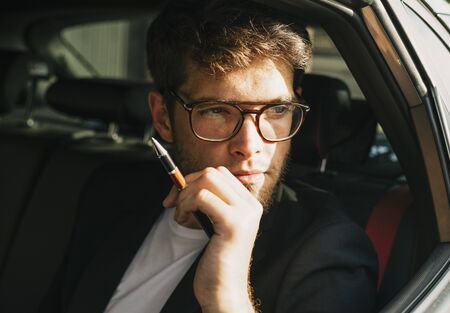 Attractive young man with a beard and glasses looks through the window of his car. Businessman.