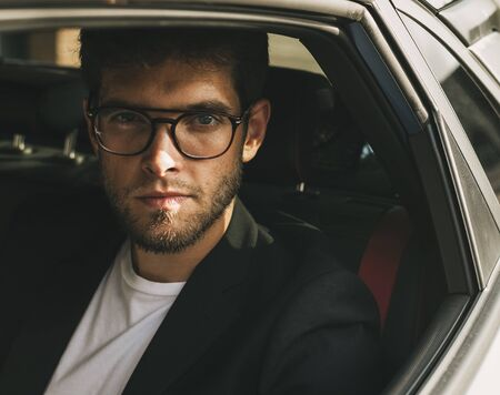 Attractive young man with beard and glasses with serious face looks at camera through the window of his car. Businessman. Stock Photo
