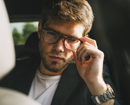 Attractive young man with beard and glasses with serious face looks at camera. Businessman. Stock Photo