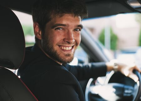 Attractive young man with a beard smiles and looks at camera in his car.