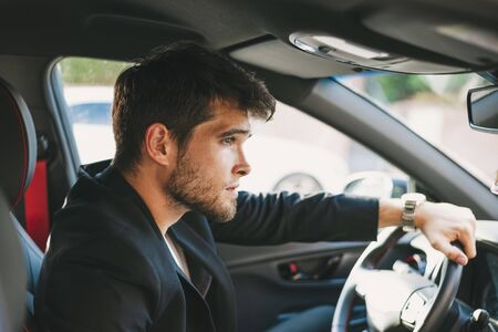 Attractive young man with a beard is serious while driving.