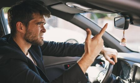 Attractive young man with a beard is very angry driving.