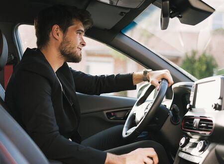 Atrakcyjny młody człowiek z brodą jeździ swoim samochodem.