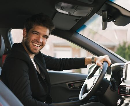 Attractive young man with a beard smiles at camera inside his car. Drive.