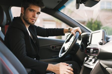 Attractive young man with a beard looks seriously at camera inside his car. Drive.
