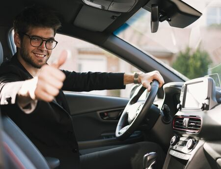 Attractive young man with a beard and glasses smiles and says ok to the camera in his car.