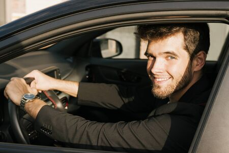 Attractive young man with a beard smiles and looks at camera sitting in his car.