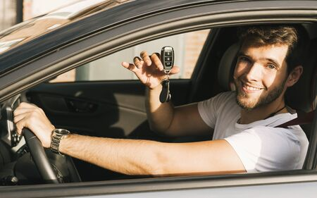 Attractive young man with a beard teaches the camera the keys of his new car.