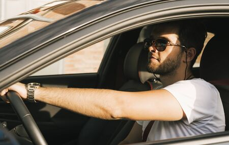 Attractive young man with a beard and sunglasses drives his car.
