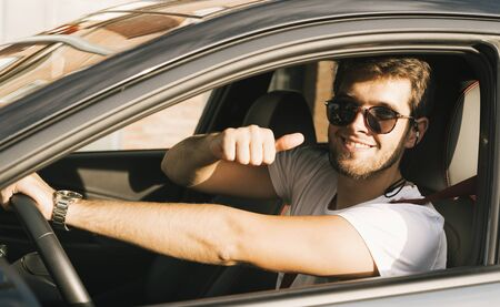 Attractive young man with beard and sunglasses says ok to camera with his hand.Sun