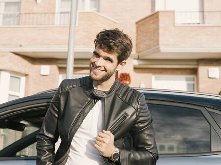 Attractive young man with a beard smiles at camera and leans on his car. Stock Photo