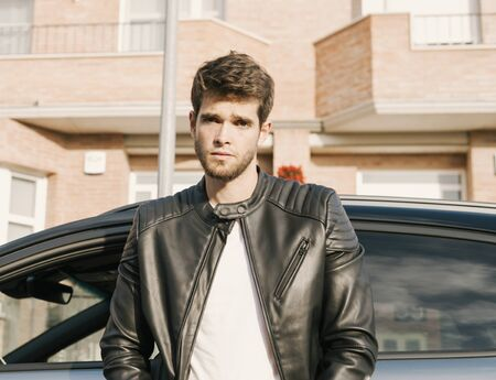 Attractive young man with a beard looks seriously at the camera while leaning on his car