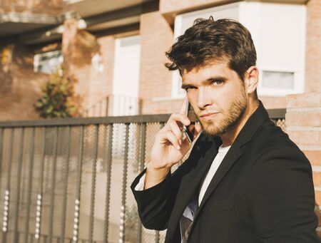 Close-up of attractive young man with beard in suit speaks on the phone looking at camera