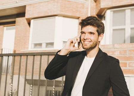 Close-up of attractive young man with beard in suit speaks on the phone and smiles.