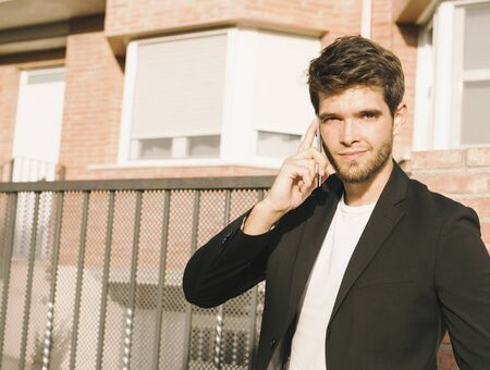 Close-up of attractive young man with beard in suit talks on the phone and smiles while looking at camera. Stock Photo