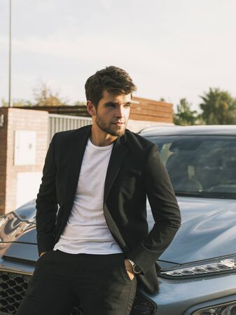Close-up of attractive young man with beard in suit leaning on his car.suit Stock Photo