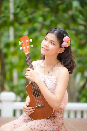 Asian girl with ukulele guitar outdoor in happy concept photo