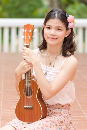 Asian girl with ykulele guitar outdoor in happy concept photo