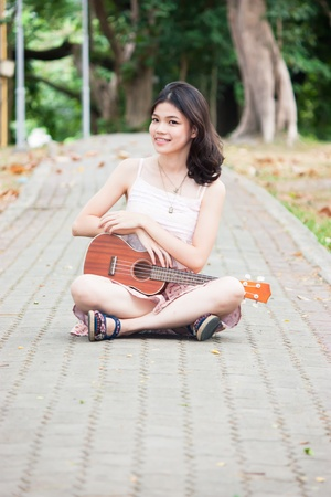 Asian girl with ukulele guitar outdoor in happy concept Stock Photo - 20595874