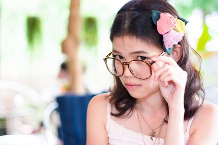 Portrait cute asian girl wearing glasses and finger on glasses photo
