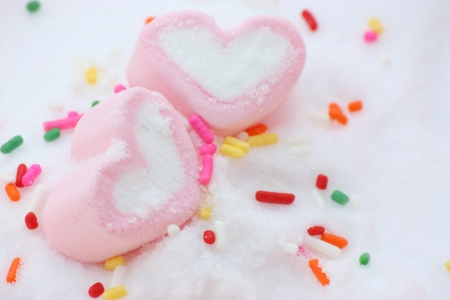 pair if pink heart shape marshmallows around by rainbow candy on snow photo