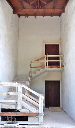 home renovation with concrete stairs and handrails provisory with axes and wooden beams photo