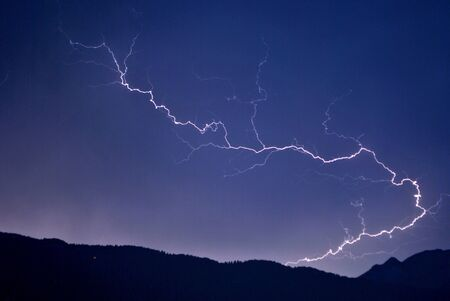 lightning in the night sky background of the Dolomites mountains