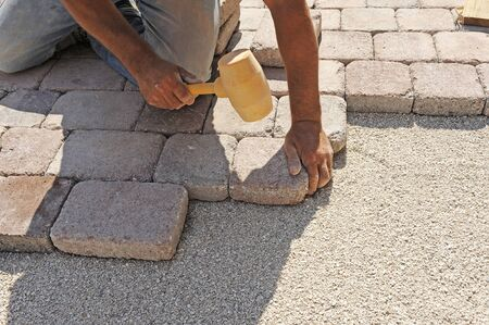 man at work paving stones with rectangular photo