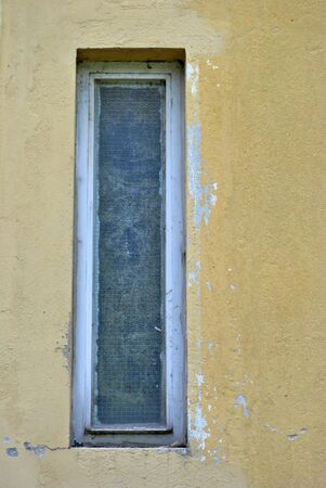 rectangular window with opaque glass and dirt on the wall color photo