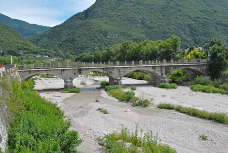 river of clear water with vegetation in the dry stream bed with bridge photo