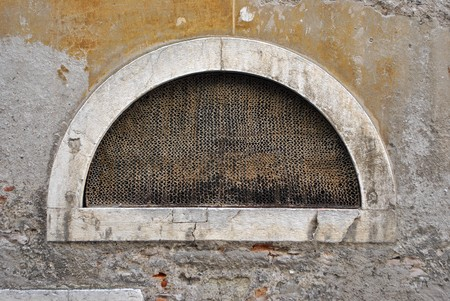 crescent-shaped window with safety net and the wall crumbling photo