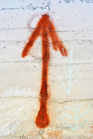 Graffiti on a wall of cement  red arrow photo