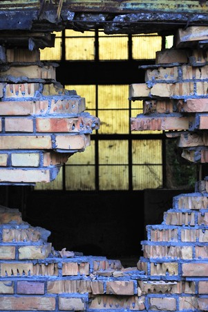 hole in the wall of red brick with concrete background blue plastic pellets photo