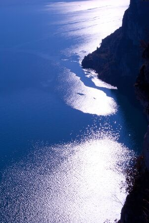 Lake Garda at sunset in the background the mountains Stock Photo
