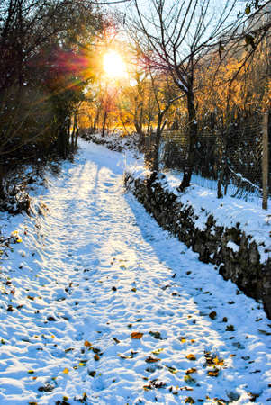 sunset with sun on snowy mountain road Stock Photo - 8351650