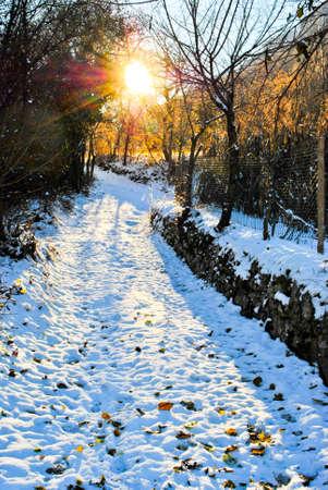 sunset with sun on snowy mountain road photo