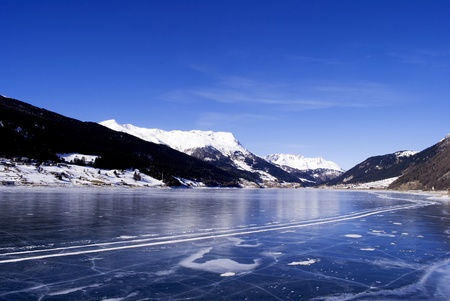 frozen lake: frozen lake in winter with the Alpine mountains and blue sky