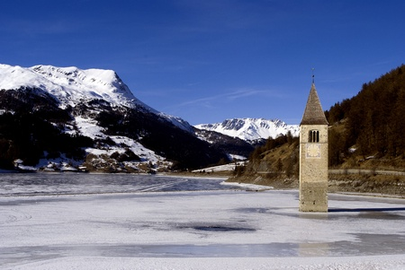 alpine lake with a bell tower in the ice, Reschensee photo