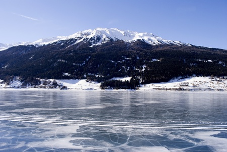 frozen lake in winter with the Alpine mountains and blue sky photo
