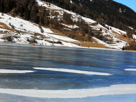 frozen lake in winter with blue sky and snow-capped mountains, Reschensee Stock Photo - 8954889
