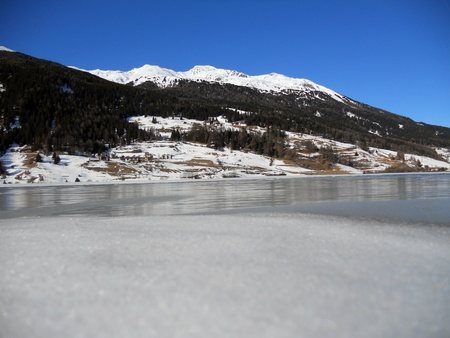 frozen lake in winter with blue sky and snow-capped mountains, Reschensee Stock Photo - 9022110