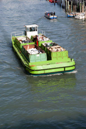 waste management: Empty boat for transporting garbage cruising in a river, used for waste management