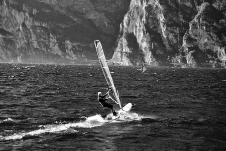 watersport: windsurfer panorama silhouette against a sparking  lake of Garda, in Trentino. Italy