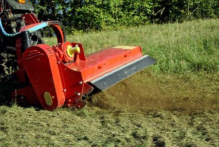 hogging: Small farm tractor bush hogging on a grass field in Trentino Alto Adige. Italy Stock Photo