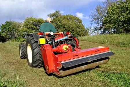 Small farm tractor bush hogging on a grass field in Trentino Alto Adige. Italy Stock Photo