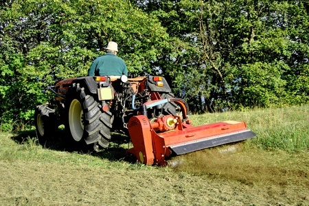 Small farm tractor bush hogging on a grass field in Trentino Alto Adige. Italy Editorial