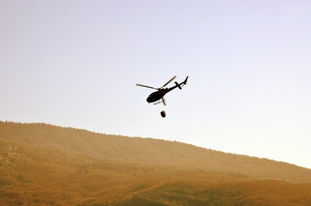A helicopter dropping water on a fire.  photo