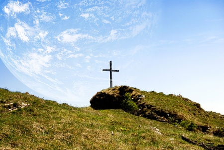 catholic cross in the mountains with planet Earth photo