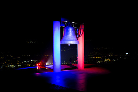 deadly: ROVERETO, ITALY - NOVEMBER 16, 2015: The great Peace Bell Dolens Mary  lit up with the Tricolor in a show of support for the people of France following the deadly terrorist attacks in Paris.