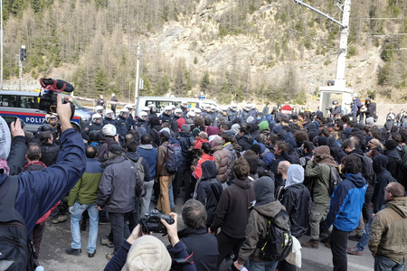 responds: MATREI AM BRENNER, AUSTRIA - 03 APRIL 2016: Moments of tension between no-borders and Austrian police, unprepared for that event, he responds with pepper spray to ward off protesters that tried to advance further in Austria.